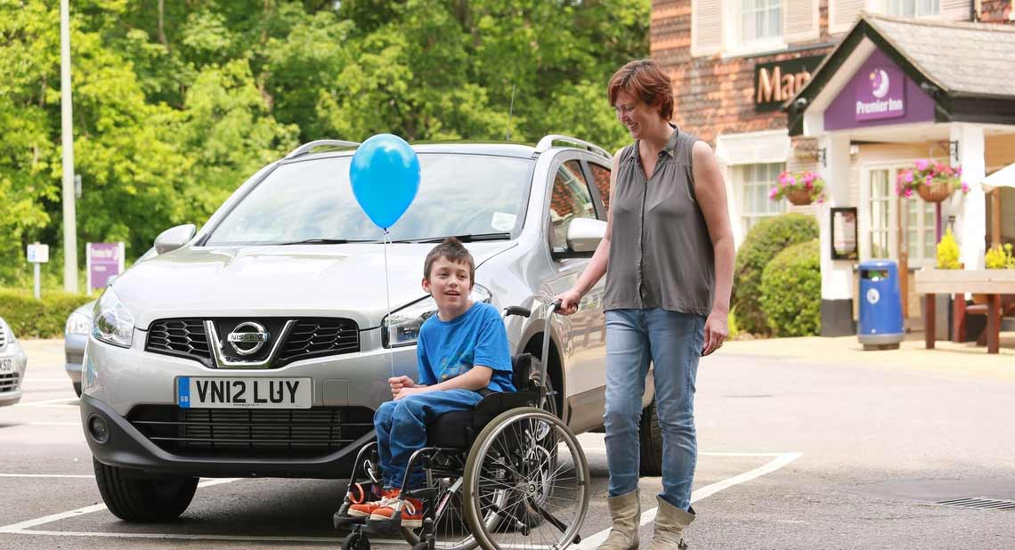 Happy mother and son with their mobility car