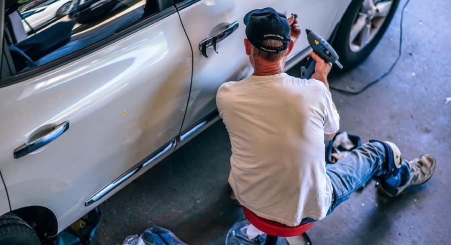 Man working on a car door