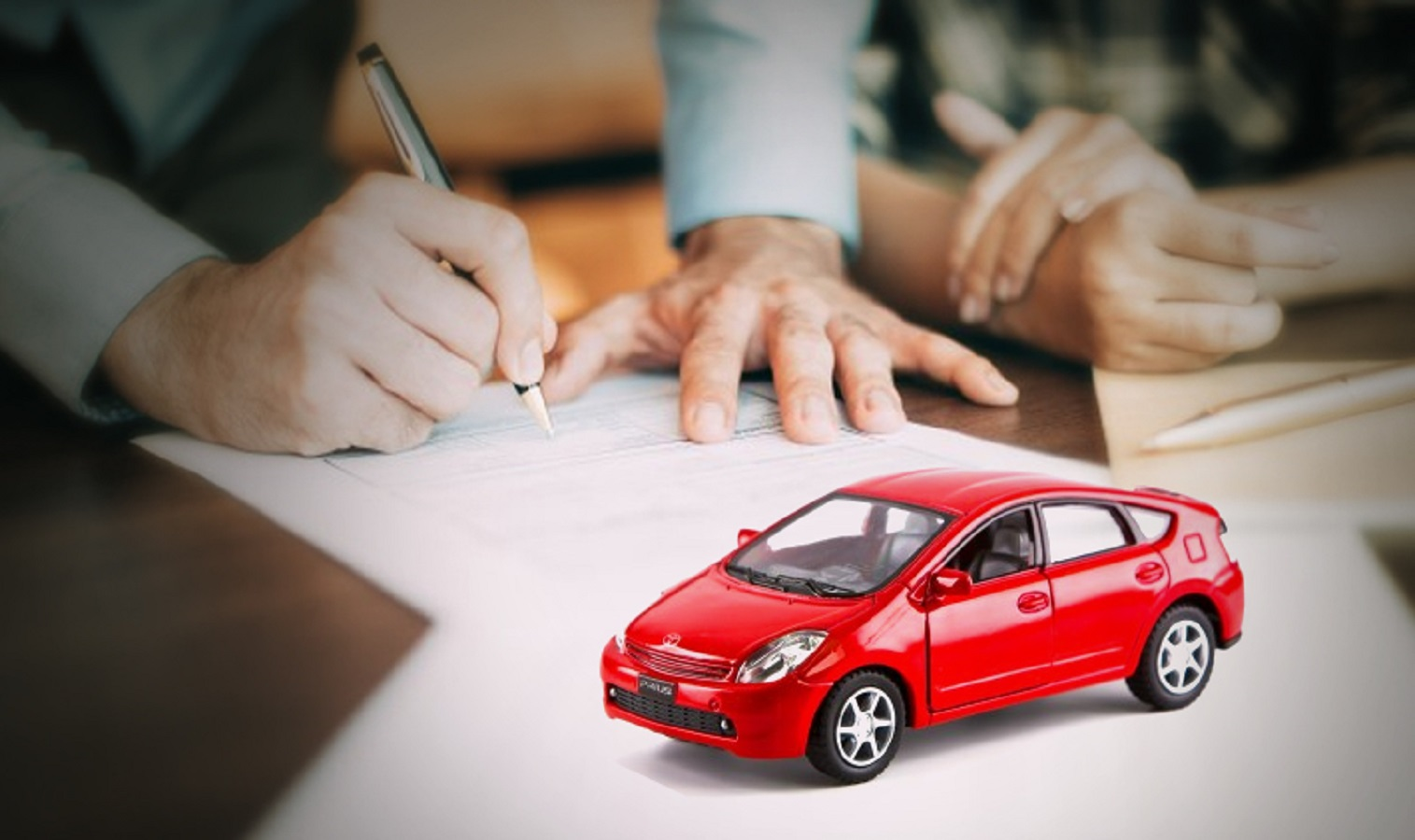 Toy car on a desk with paper work