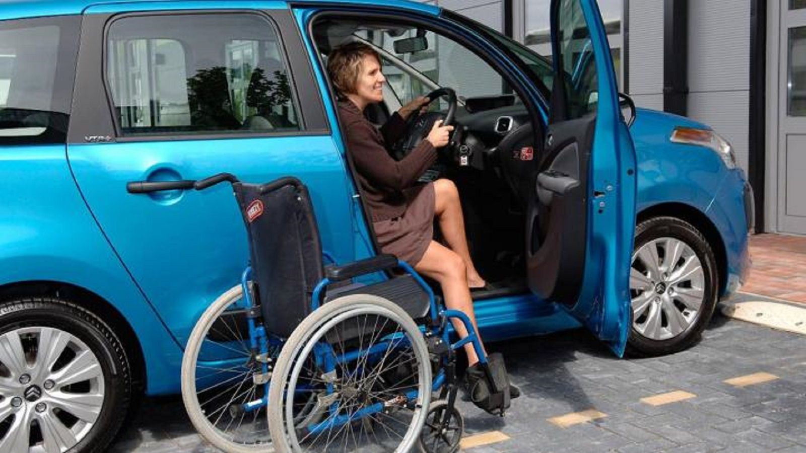 Lady climbing out a Motability vehicle
