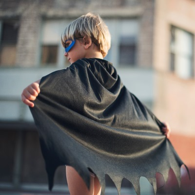 A young Batman with cape unfurled